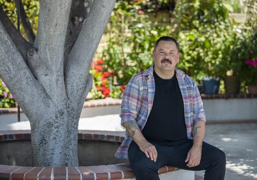 Gustavo Hernandez sitting in his mom's yard in Santa Ana.