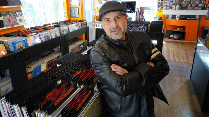 Standing among a shop full off record music albums, Eric Howarth is one of the co-owners of the Viny