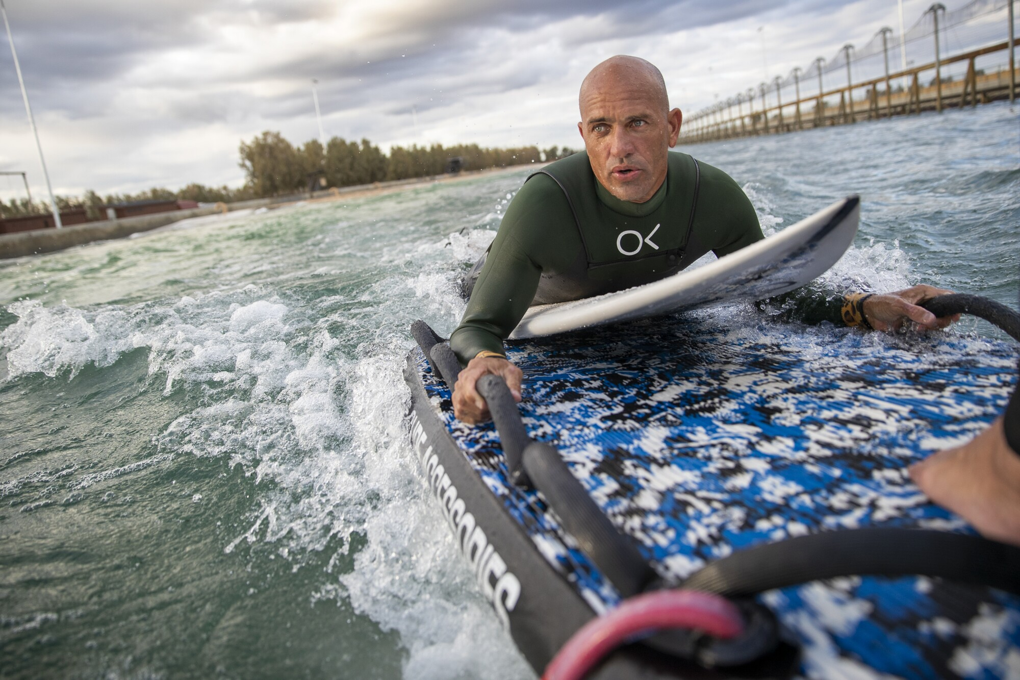 """Kelly Slater is taken out to his surfing position on the back of a wave runner during production on """"The Ultimate Surfer."""""""