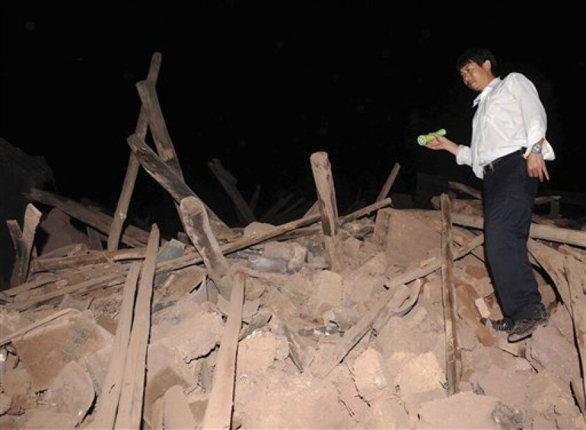 In this photo released by China's official Xinhua news agency, a man stands on the debris of a collapsed house in Yao'an County, Chuxiong Yi Autonomous Prefecture in southwest China's Yunnan Province early Friday July 10, 2009 after a magnitude-6.0 temblor rocked parts of Yunnan province Thursday evening, July 9. (AP Photo/Xinhua, Lin Yiguang)