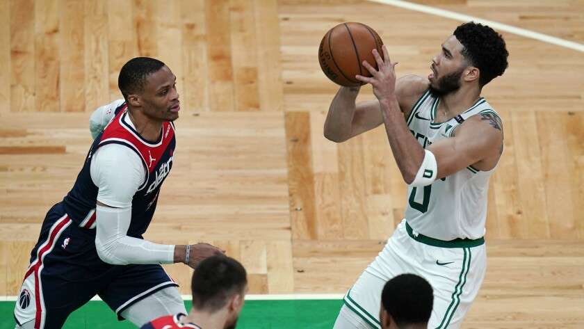 Boston Celtics forward Jayson Tatum (0) sets to shoot against Washington Wizards guard Russell Westbrook, left, during the second half of an NBA basketball Eastern Conference play-in game Tuesday, May 18, 2021, in Boston. (AP Photo/Charles Krupa)