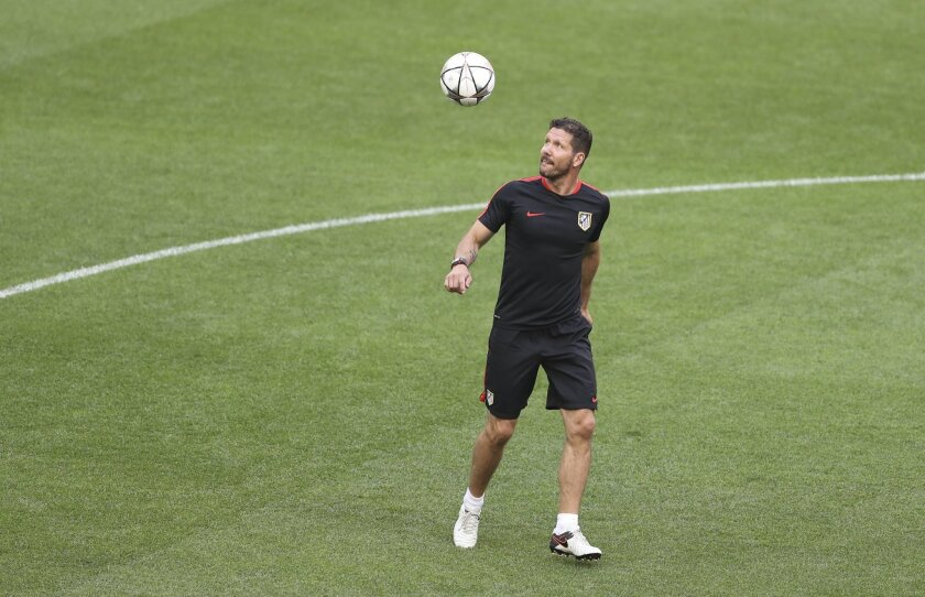 Atletico's coach Diego Simeone looks at the ball as he leads a training session at the San Siro stadium in Milan, Italy, Friday, May 27, 2016. The Champions League final soccer match between Real Madrid and Atletico Madrid will be held at the San Siro stadium on Saturday, May 28. (AP Photo/Antonio
