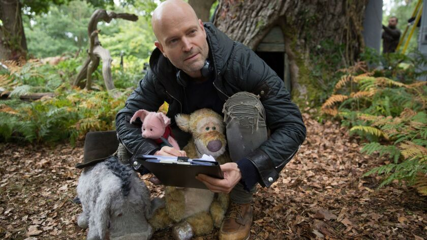 "Marc Forster with Eeyore, Piglet and Tigger on the set of ""Christopher Robin."""