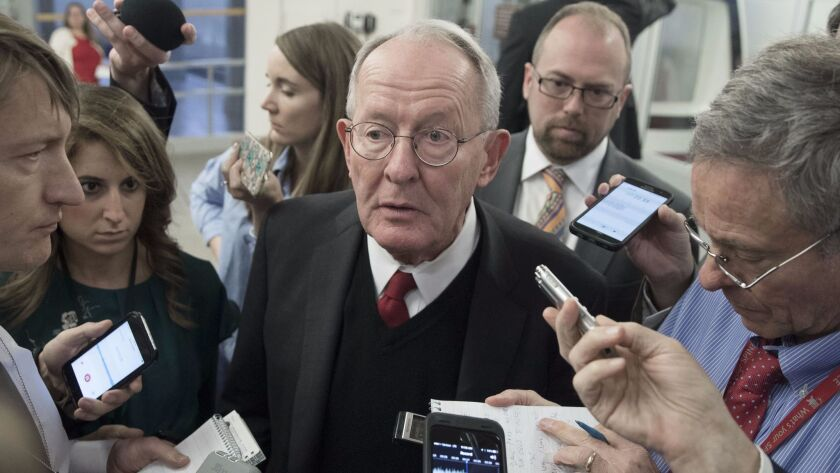 Republican Sen. Lamar Alexander talks to reporters on Oct. 19. His bipartisan compromise on Obamacare with Democratic Sen. Patty Murray is still awaiting a vote.