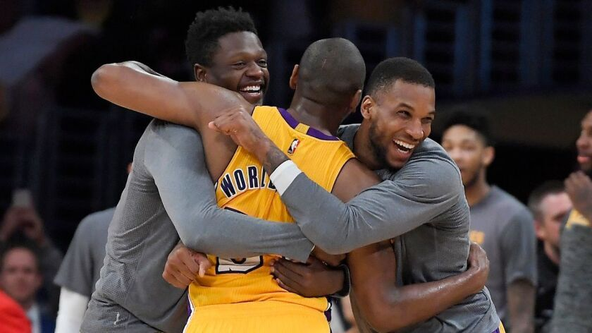 Lakers forward Metta World Peace, center, is hugged by forwards Julius Randle, left, and Thomas Robi
