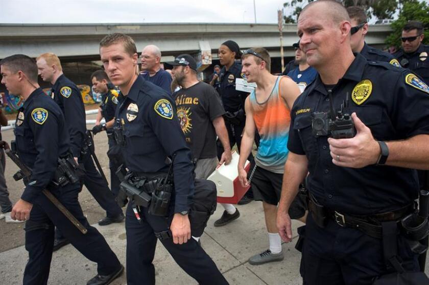 Un grupo de cinco hombres son escoltados por un contingente de policías después de que estén rodeados por una gran multitud de activistas pro-parque, el domingo 03 de septiembre de 2017, tras las alertas distribuidas en internet respecto a grupos de extrema derecha que pretendían atacar los murales del lugar, en el Barrio Logan, en San Diego (EE.UU.). EFE/Archivo