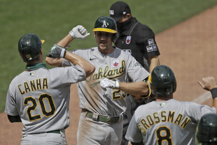 Oakland Athletics' Stephen Piscotty, center, celebrates with Mark Canha (20) and Robbie Grossman (8) after hitting a three-run home run off San Francisco Giants' Dereck Rodriguez in the fifth inning of a baseball game Sunday, Aug. 16, 2020, in San Francisco. (AP Photo/Ben Margot)