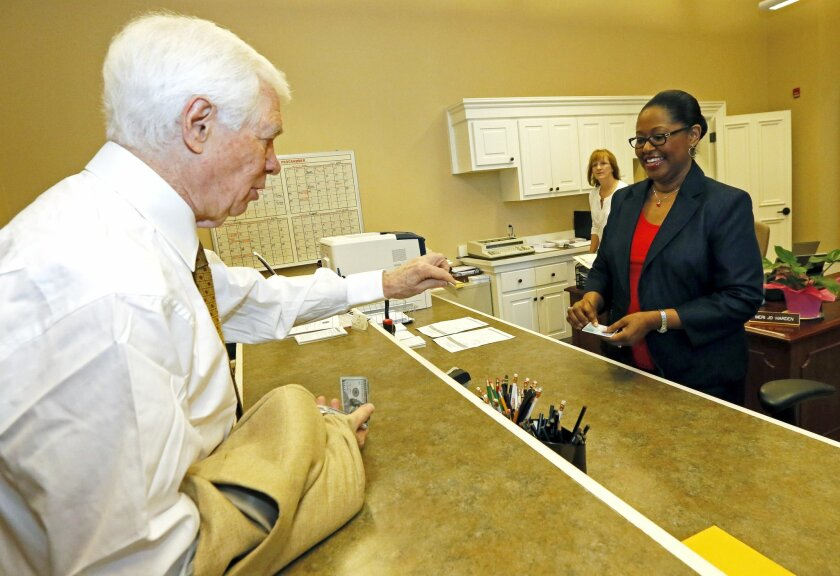 U.S. Sen. Thad Cochran, R-Miss., left, presents his photo identification to Baretta Mosley, the Lafayette County Circuit Clerk, prior to voting absentee in Oxford, Miss., Saturday, May 31, 2014. Cochran, 76, in Congress since 1973, is in the fight of his political life, a brutal, too-personal Republican primary that has drawn his bedridden wife into the melee and resulted in criminal charges against some of his opponent's supporters. (AP Photo/Rogelio V. Solis)