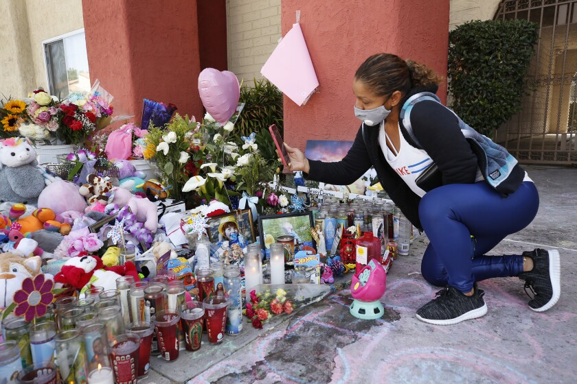 Kneeling next to candles, stuffed animals and flowers, a woman holds up her phone.
