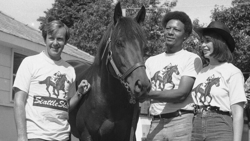 Seattle Slew stands with owners Mickey, left, and Karen Taylor and groom John Preston at the Belmont stables on June 12, 1977.