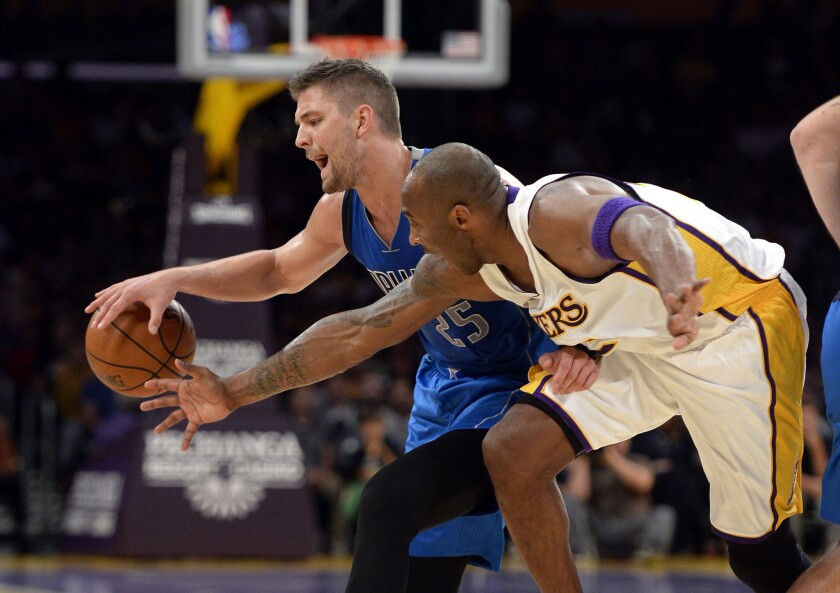 Lakers forward Kobe Bryant, right, attempts to steal the ball from Dallas Mavericks' Chandler Parson in the first half at the Staples Center on Sunday.