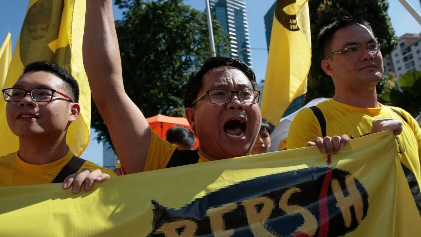 Malaysian protesters chant in the streets of Kuala Lumpur to pressure Prime Minister Najib Razak to resign.