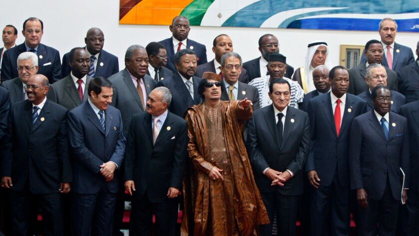 Libyan leader Moammar Gadhafi, center, gestures during a group picture with Arab and African leaders