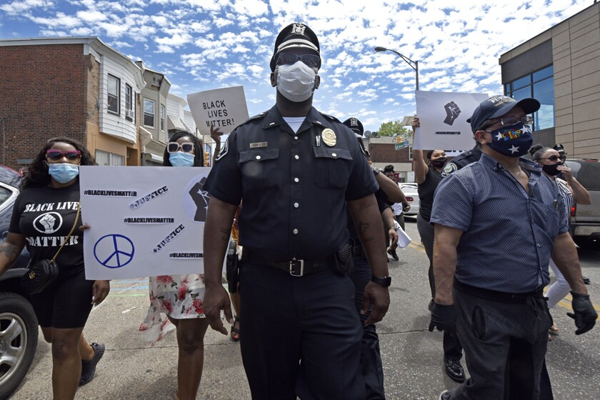 Lt. Zack James of the Camden County (N.J.) Metro Police Department marches along with demonstrators in Camden on Saturday to protest the death of George Floyd.