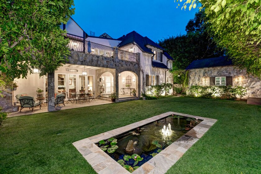 The 1930s English Tudor-style home, designed by architect James Dickason, features a heated patio, reflecting pool and a large second-story terrace.