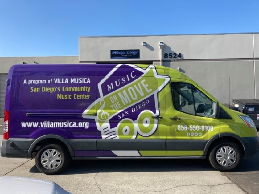 Picture of a decorated van with information about music program
