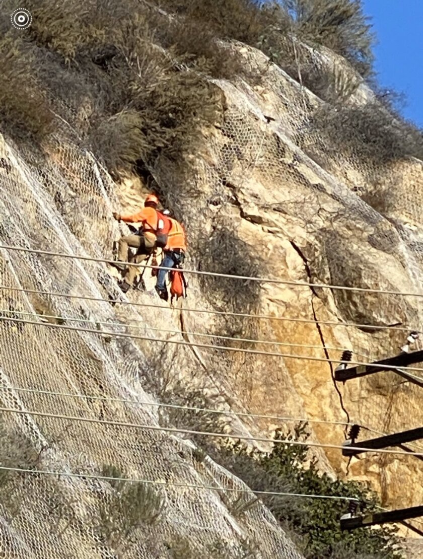 CalTrans workers climb up the hillside in the 1100 block of Laguna Canyon Road to remove unsteady boulders on Friday.