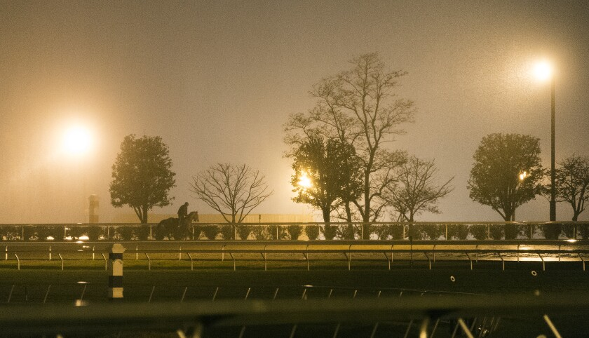 Rain falls as a horse makes its way around the track at Keeneland during Breeders' Cup workouts on Oct. 28, 2015, in Lexington, Ky.