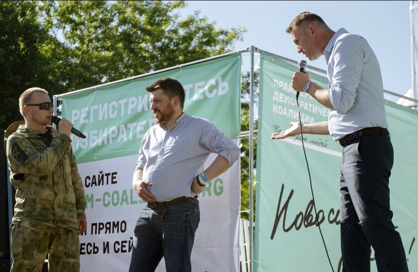 FILE - In this Sunday, June 7, 2015, file photo, Russian opposition activist and blogger Alexei Navalny, right, argues with a man in a military uniform, left, as opposition activist Leonid Volkov, center, listens during a rally in a park that attracted several hundred people in Novosibirsk, Siberia's biggest city, Russia. Leonid Volkov, campaign chief for the opposition, along with two other candidates, began hunger strike on Tuesday July 28, 2015 to protest authorities' decision to disqualify them from a local election in Russia's third-largest city. (AP Photo/Alexander Lukin, File)