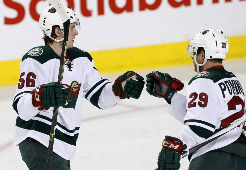Minnesota Wild's Eric Haula, (56) from Finland, celebrates his goal against the Calgary Flames with teammate Jason Pominville during the first period of an NHL hockey game Wednesday, Feb. 17, 2016, in Calgary, Alberta. (Larry MacDougal/The Canadian Press via AP)