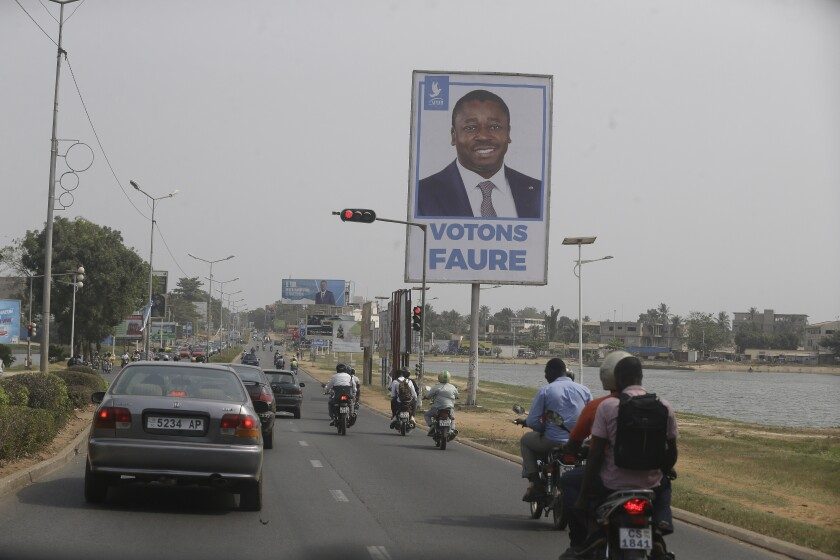 Cars drive past election posters of Togo's Incumbent President Faure Gnassingbe, Presidential Candidate of Union for the Republic, on the street in Lome, Togo Friday, Feb. 21, 2020. The West African nation of Togo is voting Saturday in a presidential election that is likely to see the incumbent re-elected for a fourth term despite years of calls by the opposition for new leadership. (AP Photo/Sunday Alamba)