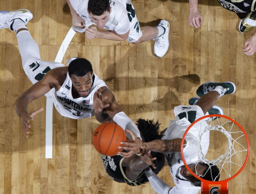 Michigan State's Xavier Tillman, left, and Marcus Bingham Jr., right, reach for a rebound with Western Michigan's Titus Wright, center, as Michigan State's Foster Loyer, top, watches, during the second half of an NCAA college basketball game, Sunday, Dec. 29, 2019, in East Lansing, Mich. Michigan State won 95-62. (AP Photo/Al Goldis)