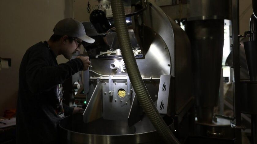 Tony Hasapis smells a batch of coffee being roasted at Two Brothers' brewing warehouse in Warrenville on Nov. 1, 2018.