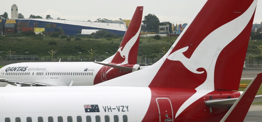 FILE - In this Feb. 26, 2015, file photo, a Qantas plane maneuvers behind another parked at a gate at Sydney Airport in Sydney. Qantas Airways chief executive Alan Joyce said on Thursday, Feb. 25, 2021, he doesn't expect his airline will resume international travel except for New Zealand until late October, after the Australian population is vaccinated for COVID-19. (AP Photo/Rick Rycroft, File)