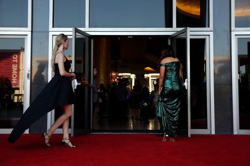 Women in gowns enter open theater doors.