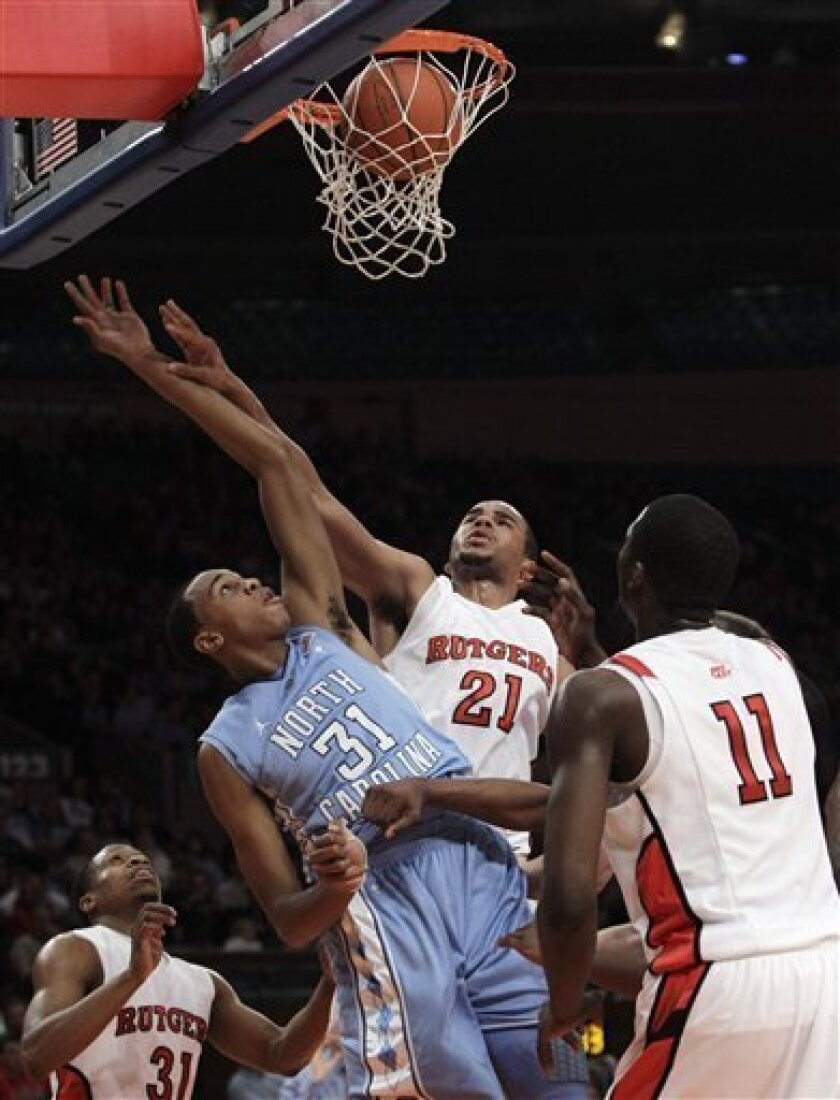 North Carolina's John Henson (31) watches his shot after tipping it in for two points as Rutgers' Austin Johnson (21) defending and Dane Miller (11) wait for a rebound during the first half of an NCAA college basketball game at Madison Square Garden in New York, Tuesday, Dec. 28, 2010. (AP Photo/Ka