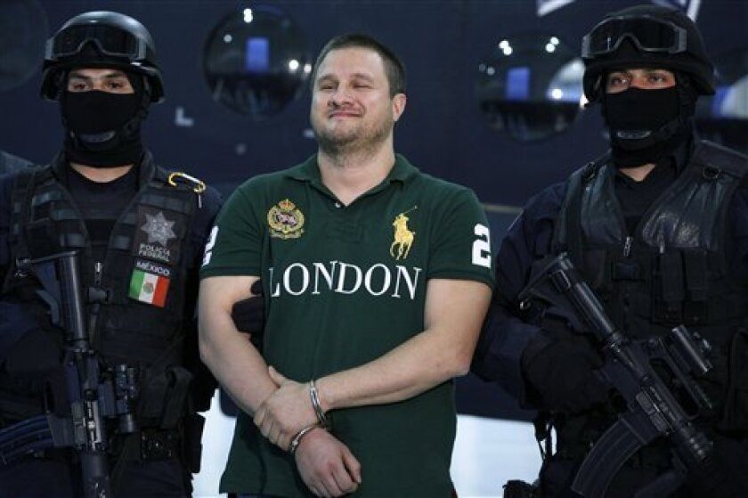 "FILE -  In this Aug. 31, 2010 file photo, Texas-born fugitive Edgar Valdez Villarreal, alias ""the Barbie,"" center, smiles during his presentation to the press after his arrest in Mexico City. ""Narco Polo'' is the new fashion trend sweeping lower-class neighborhoods in Mexico, after seven high-ranki"