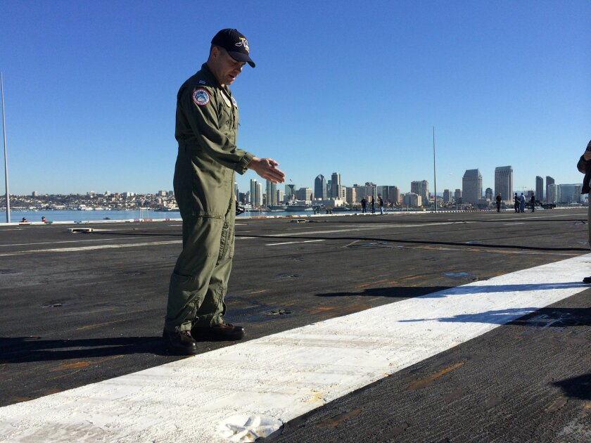 Lt. Rick Dorsey points to the place on the USS Nimitz flight deck where an F-35C would aim to hit later that day, Nov. 3, to make the first Joint Strike Fighter carrier landing. The goal was for the plane's tailhook to catch the third wire stretched across the deck, just to the right of Dorsey. It