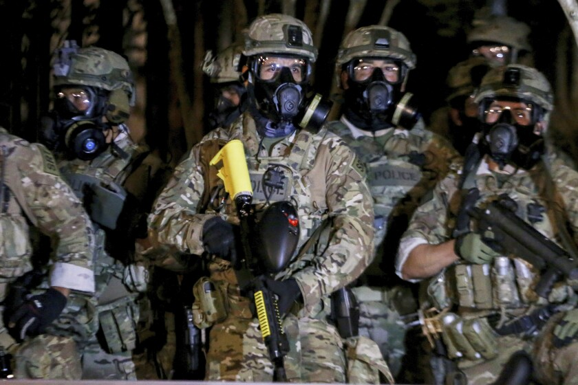 Federal officers wear camouflage uniforms and gas masks while patrolling Portland, Oregon