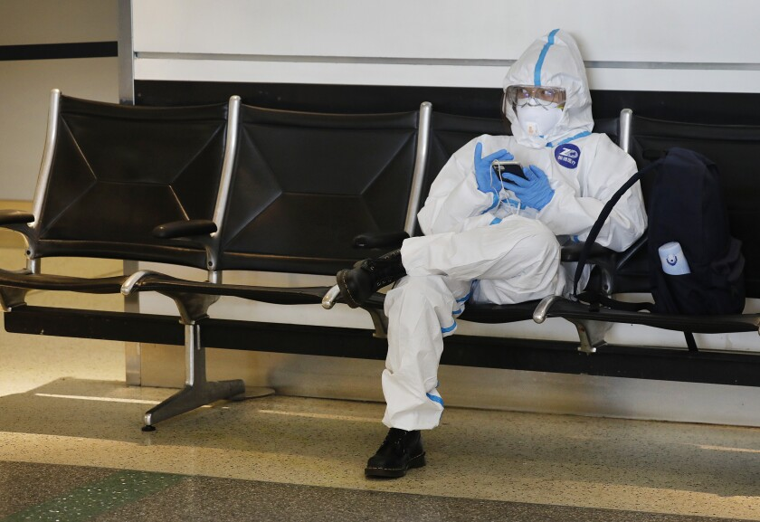 A Chinese student wearing protective gear waits for a flight home at Los Angeles International Airport in May.