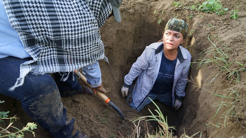 Martha Gonzalez, 58, searches inside a suspected grave in Veracruz, Mexico. Her son, a municipal policeman, disappeared in 2013.