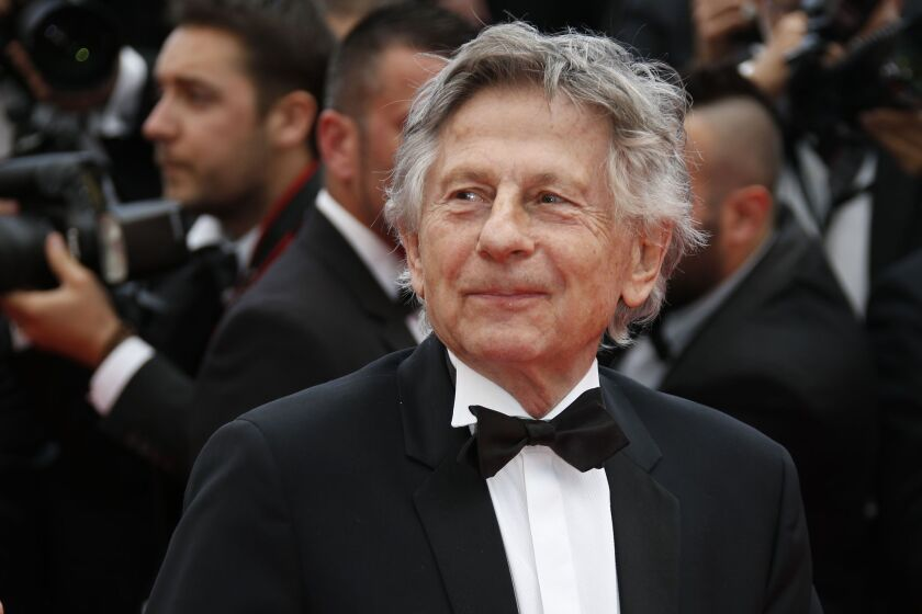 "Roman Polanski poses for photos as he arrives for the screening of the film ""Saint-Laurent"" at the 67th edition of the Cannes Film Festival on May, 17, 2014."