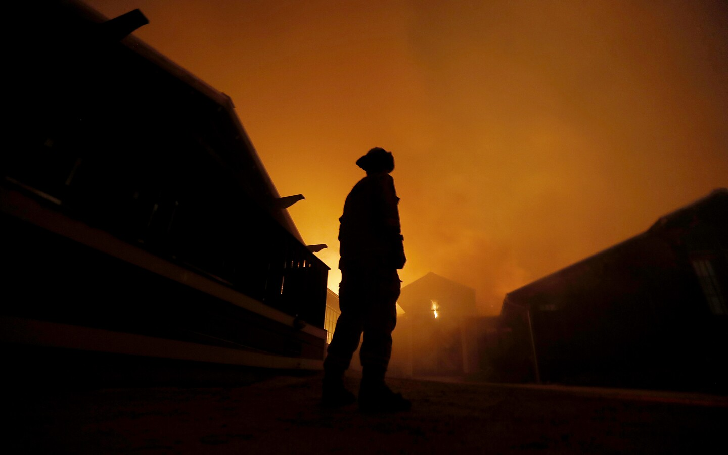 A firefighter looks on as trhe Soda Ranch winery along State Highway 128 near Healdsburg is consumed by the Kincade fire early Sunday morning, Oct. 27, 2019.