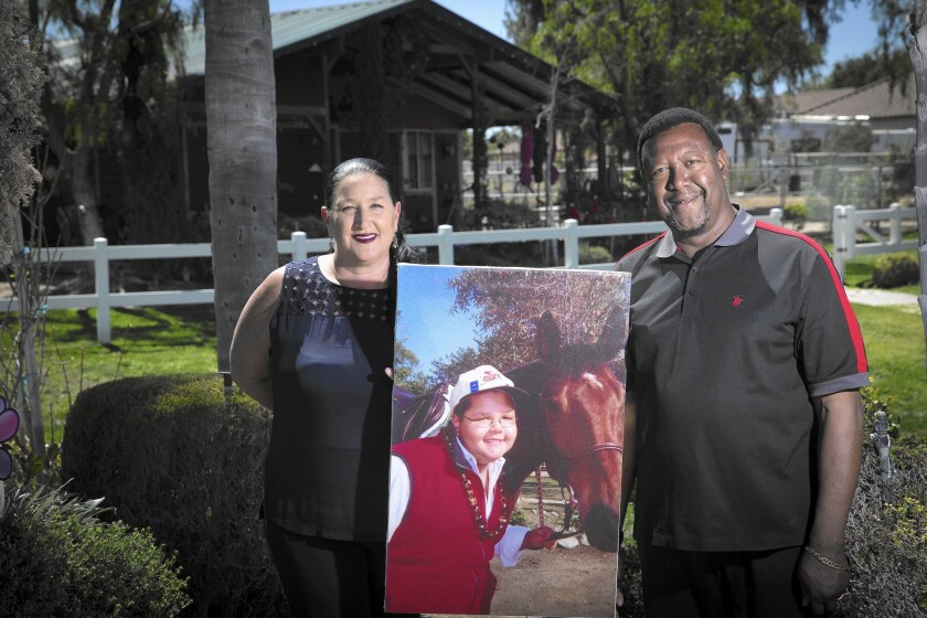 Carole and Ty Moss hold a photo of their son, Nile, who died at age 15 after he went to an Orange County hospital for an MRI and got infected with a superbug. A law giving the public access to limited data on infected patients was named after him.