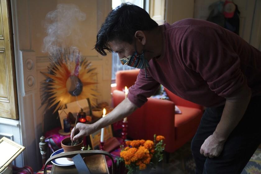 Sebastian Diaz Aguirre coloca incienso en un altar por el Día de Muertos dedicado a su padre
