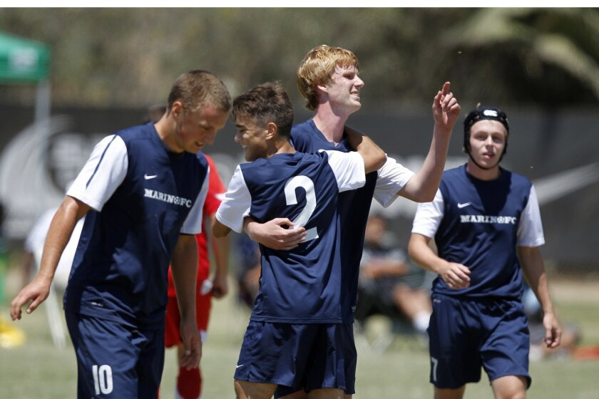 Marin FC striker Teddy Mauze (pointing) celebrates with his teammates after scoring a goal.
