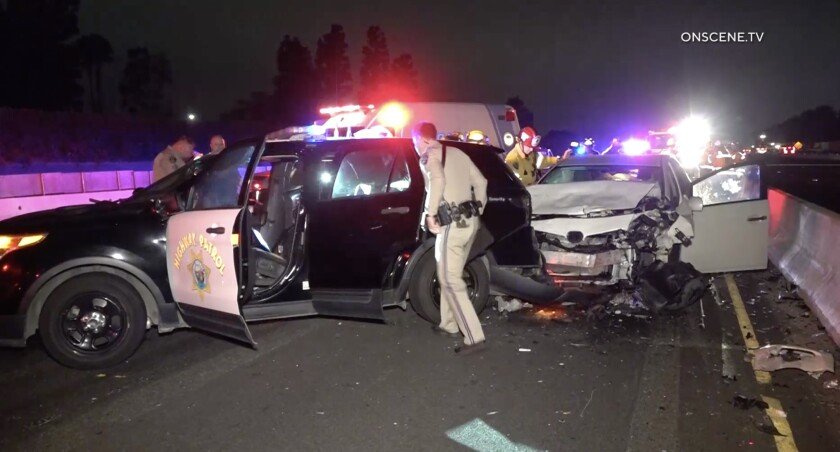 Two CHP officers were injured Friday morning when a car crashed into their cruiser on the southbound 405 Freeway in Fountain Valley.