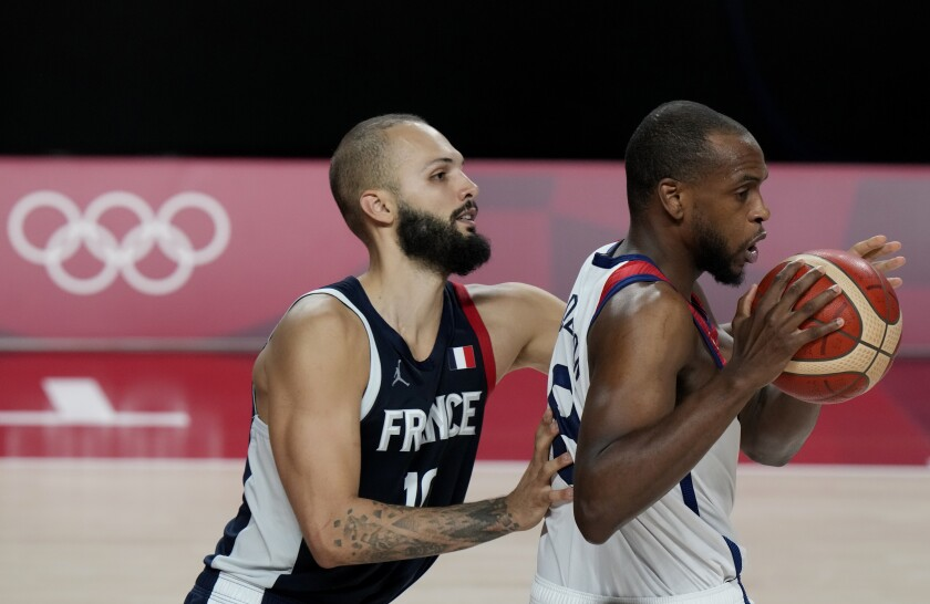 United States' Khris Middleton (8) drives ahead of France's Evan Fournier (10) during men's basketball gold medal game at the 2020 Summer Olympics, Saturday, Aug. 7, 2021, in Saitama, Japan. (AP Photo/Luca Bruno)