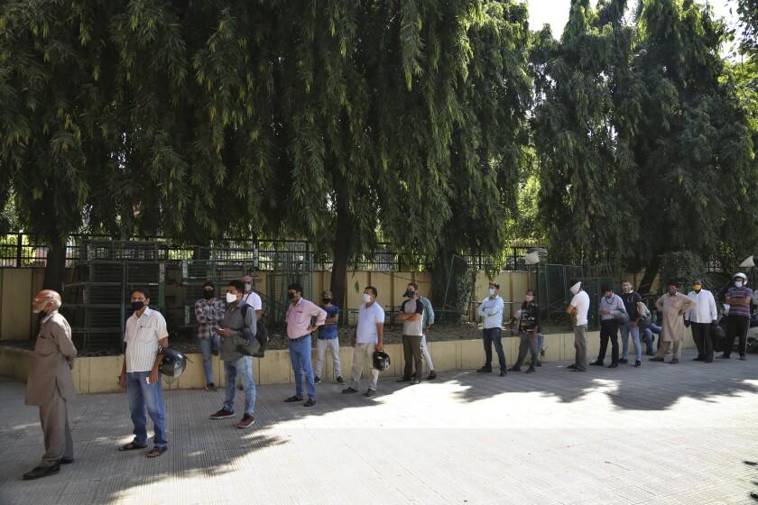 People wait for coronavirus test results in Jammu, India.