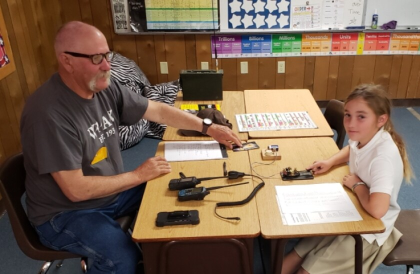 Steve Stipp, president of the Ramona Outback Amateur Radio Society, shows a 3rd grader how to use amateur radio equipment.