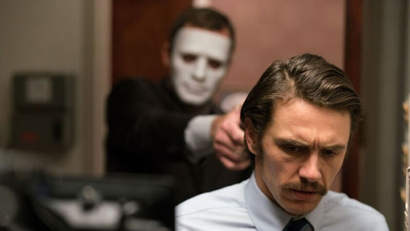"James Franco is menaced by a gunman in the movie ""The Vault."""