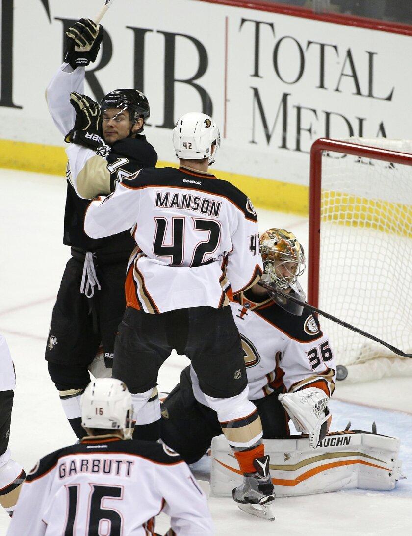 Pittsburgh Penguins' Chris Kunitz (14) celebrates his goal past Anaheim Ducks goalie John Gibson (36) with Josh Manson (42) defending during the first period of an NHL hockey game against the Anaheim Ducks in Pittsburgh, Monday, Feb. 8, 2016. (AP Photo/Gene J. Puskar)