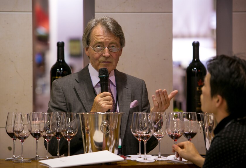 A man in a suit and tie speaks into a microphone behind several wine glasses lined up for a tasting
