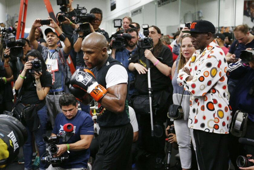 In this photo taken Thursday, April 14, 2015, Floyd Mayweather Sr., right, watches his son boxer Floyd Mayweather Jr., left, work out in Las Vegas. He taught his son to throw punches before he could walk, and he'll be in his corner for the biggest fight of his life against Manny Pacquiao on May 2. The relationship between Mayweather Sr. and his son, though, hasn't always been good. (AP Photo/John Locher)