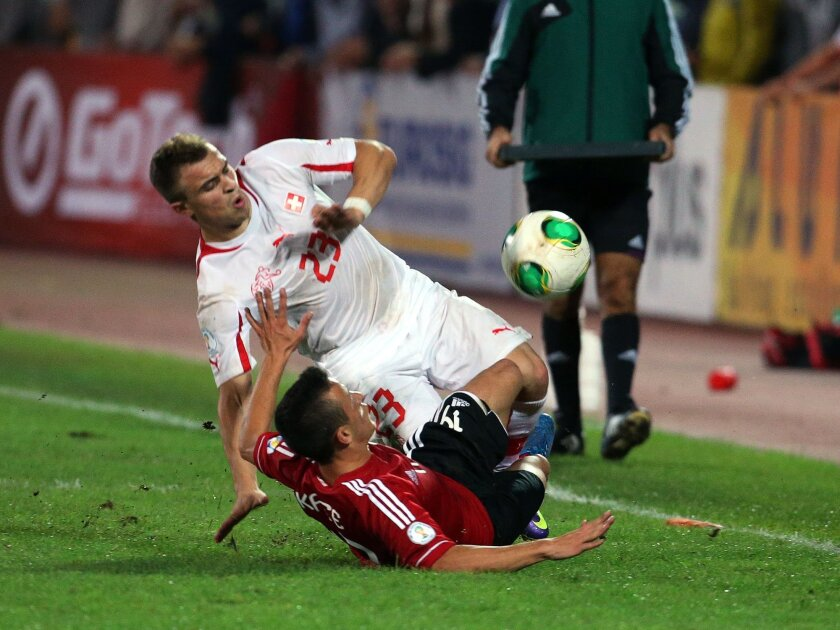 FILE - In this Friday Oct. 11, 2013, file photo, Albania's Ergys Kace, bottom, fights for the ball with Switzerland's Xherdan Shaqiri, during their World Cup Group E qualifier soccer match in Tirana, Albania. The European Championship has a reputation for being the soccer fans' favorite tournament