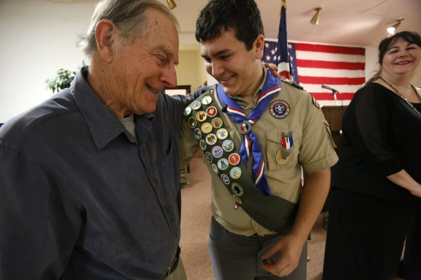 New Eagle scout David Fite, center, and his grandfather, Rich Laue, embrace each other, as David's mother, Jennifer Fite, smiles during a celebration at a Catholic church in Chicago on Sunday, Jan. 3, 2016. To earn the Boy Scout's highest rank, David earned 21 merit badges and organized a two-part